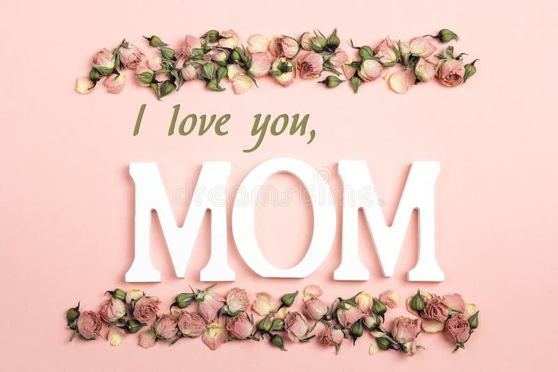 Mensaje del saludo del día de madres con las pequeñas rosas secas en backgr rosado imagen de archivo