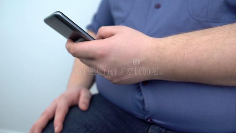Mensaje del smartphone del hombre que mecanografía gordo, programa de entrenamiento de la aptitud en línea, dieta fotos de archivo