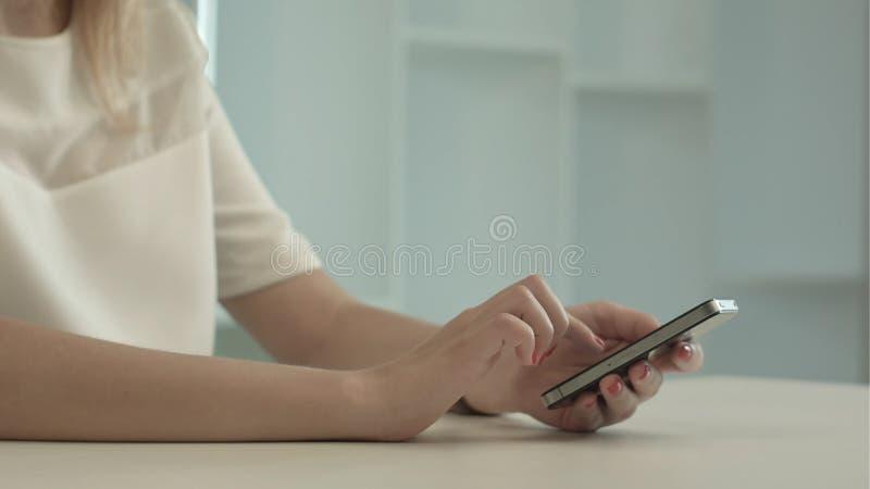 Mensaje del SMS de la escritura de la mujer joven en el teléfono móvil imagen de archivo