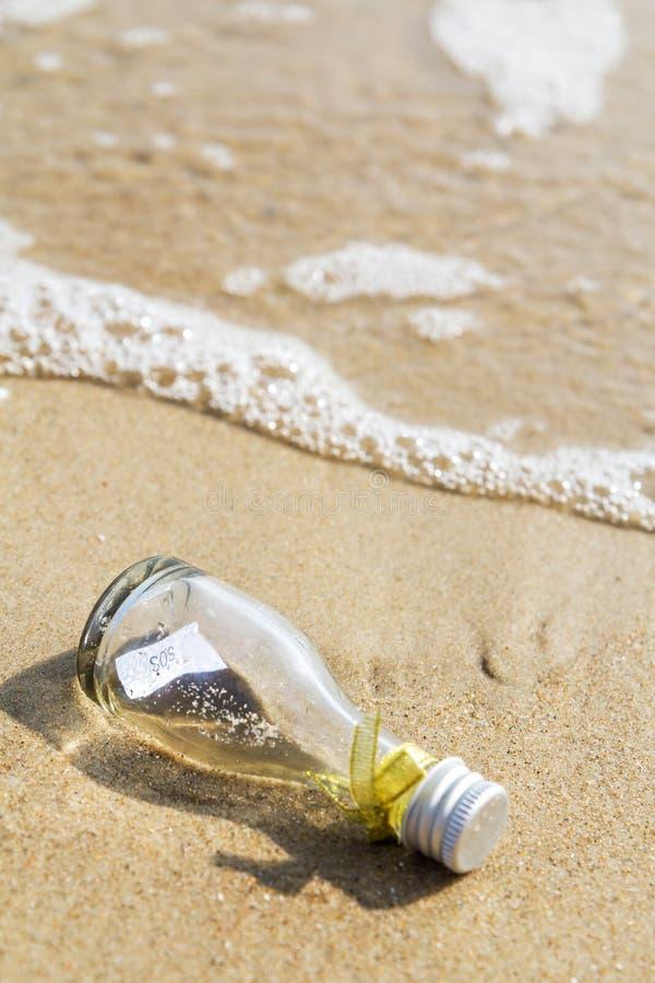 Mensaje el SOS en la botella de cristal fotos de archivo
