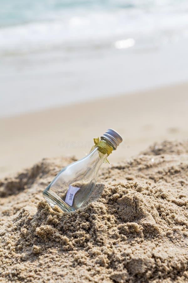 Mensaje el SOS en la botella de cristal imagenes de archivo
