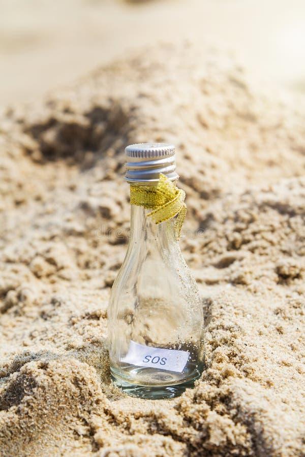 Mensaje el SOS en la botella de cristal foto de archivo libre de regalías