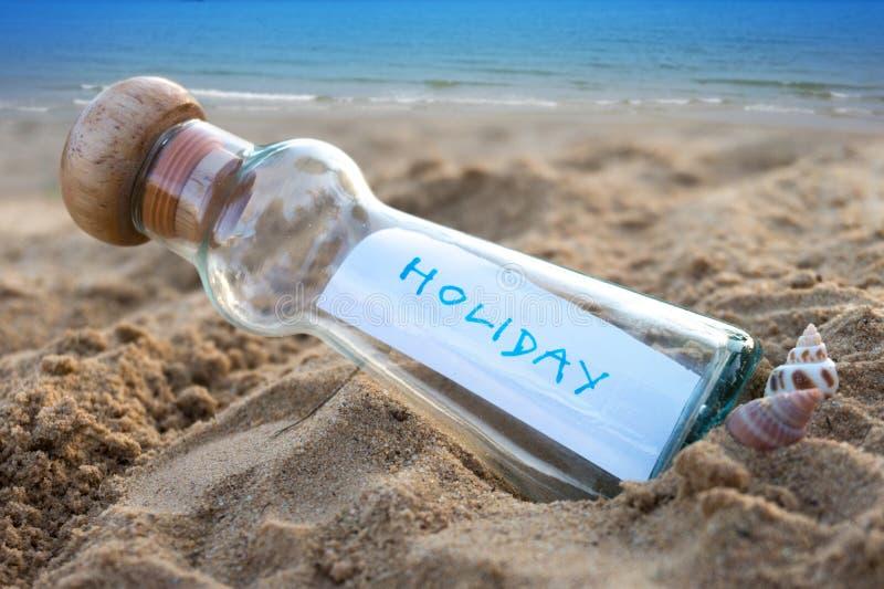 Mensaje en la botella de cristal en la arena con el fondo del paisaje marino imagenes de archivo