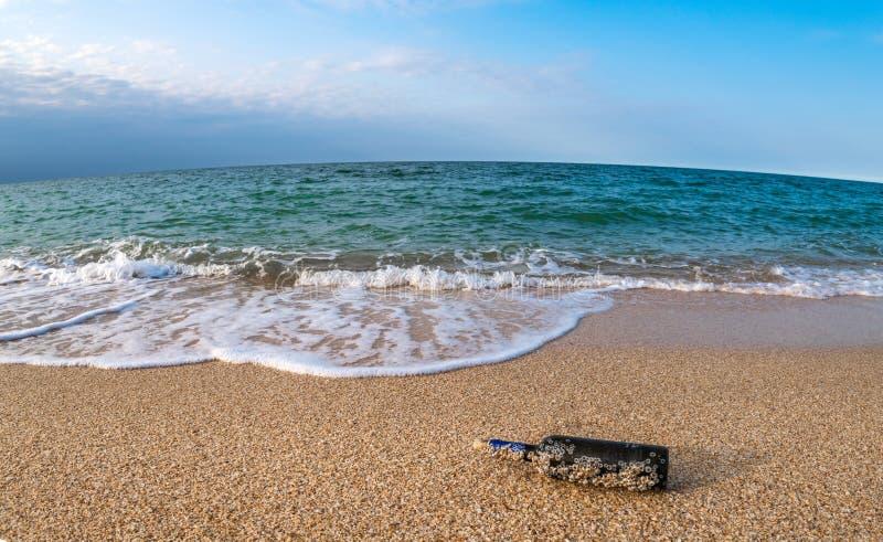Mensaje en una botella tapada con corcho en la playa vacía foto de archivo
