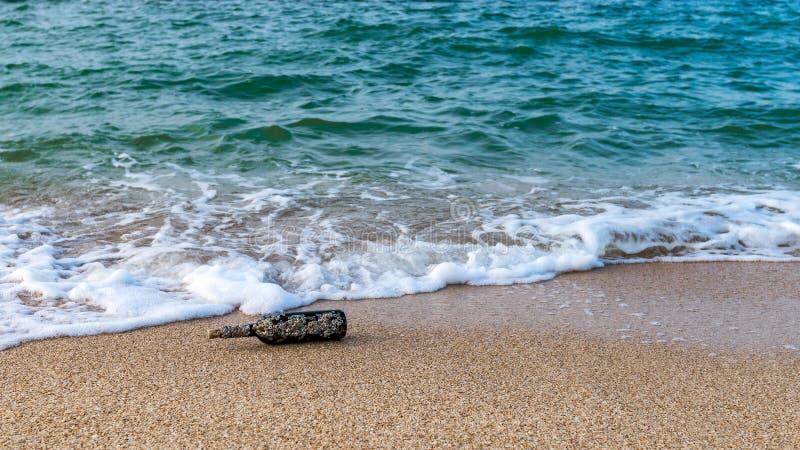 Mensaje en una botella tapada con corcho en la playa vacía fotografía de archivo