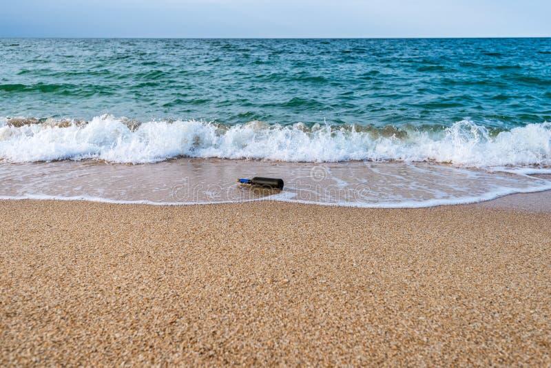 Mensaje en una botella tapada con corcho en la playa vacía fotografía de archivo libre de regalías
