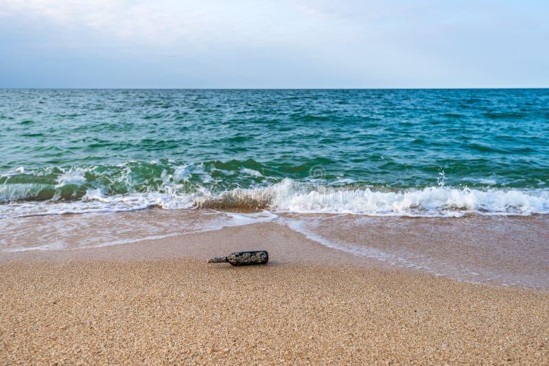 Mensaje en una botella tapada con corcho en la playa vacía fotos de archivo libres de regalías