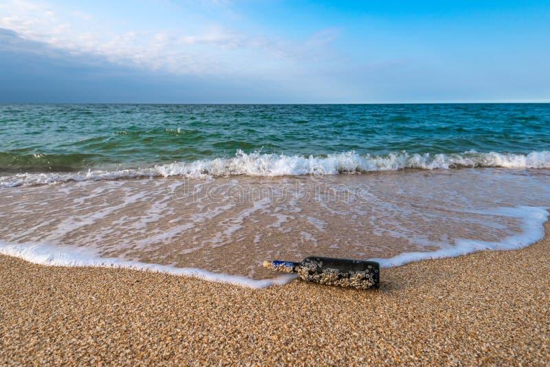 Mensaje en una botella tapada con corcho en la playa vacía imagen de archivo