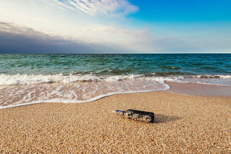 Mensaje en una botella tapada con corcho en la playa vacía fotos de archivo