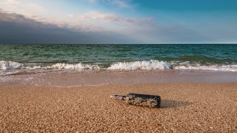 Mensaje en una botella tapada con corcho en la playa vacía imagenes de archivo