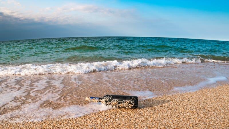 Mensaje en una botella tapada con corcho en la playa vacía foto de archivo libre de regalías
