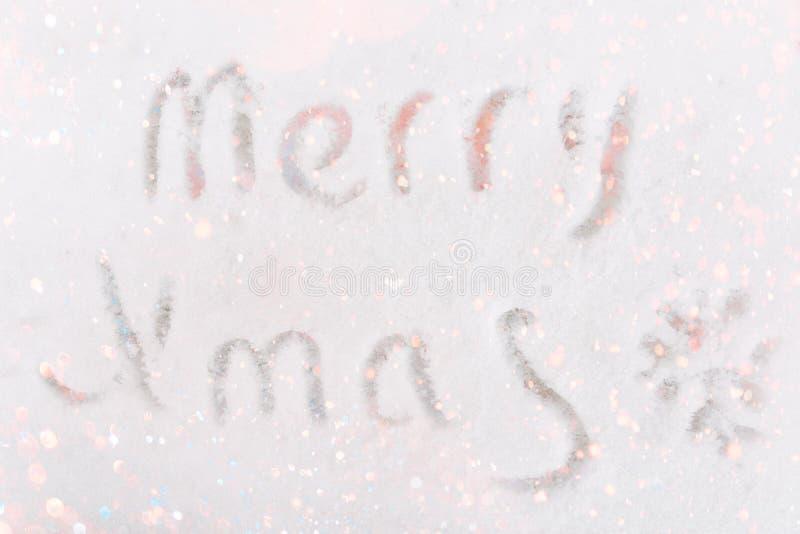 Mensaje escrito mano de la Feliz Navidad en pequeño garabato del copo de nieve del fondo blanco de la nieve Textura del brillo Ca imágenes de archivo libres de regalías