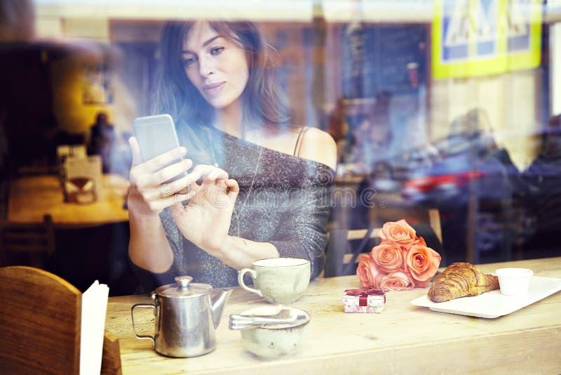 Mensaje que manda un SMS de la mujer caucásica hermosa por el teléfono móvil Desayuno del  de RomantiÑ para una fecha o un día d fotografía de archivo