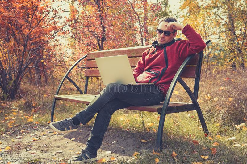 Mensaje que manda un SMS elegante joven de estudiante masculino en el ordenador port?til en parque el oto?o El individuo trabaja  fotos de archivo libres de regalías