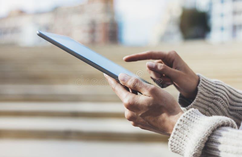 Mensaje que manda un SMS turístico del inconformista en la tableta o la maqueta de la tecnología Viajero de la persona que usa el imagen de archivo
