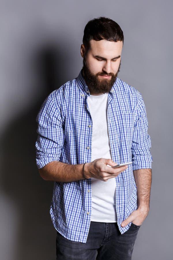 Mensaje que mecanografía del hombre barbudo relajado en smartphone foto de archivo libre de regalías