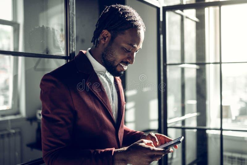 Mensaje que mecanograf?a del hombre de negocios hermoso barbudo para su esposa foto de archivo libre de regalías
