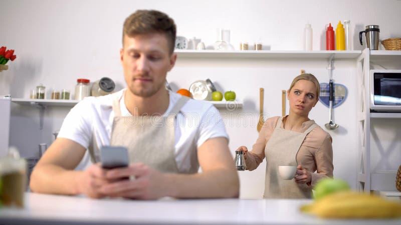 Mensaje que mecanografía del hombre hermoso en el teléfono, esposa celosa que mira furtivamente, engañando en matrimonio foto de archivo libre de regalías