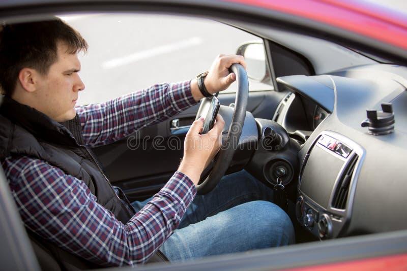 Mensaje que mecanografía del hombre joven mientras que conduce un coche foto de archivo libre de regalías