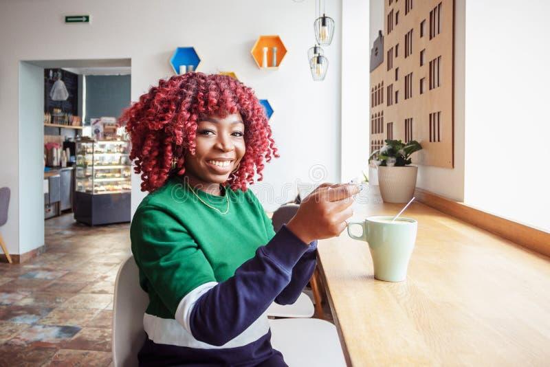 Mensaje rápido al amigo Mujer africana de moda linda que sostiene el teléfono elegante imagen de archivo libre de regalías