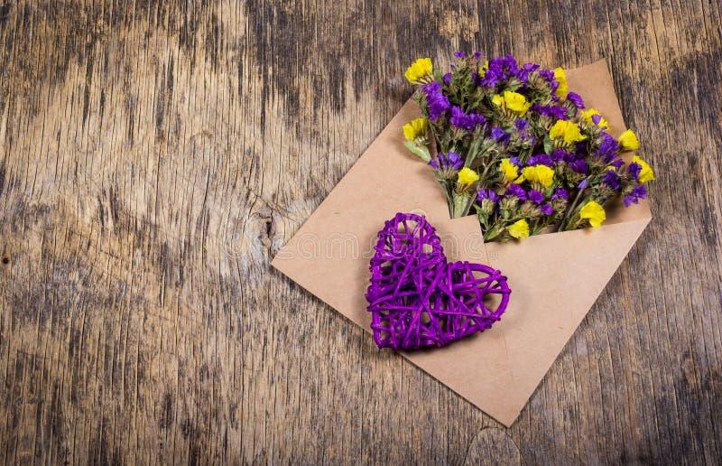 Mensaje romántico Una letra viva Flores brillantes en un sobre y un corazón de mimbre Día del `s de la tarjeta del día de San Val foto de archivo