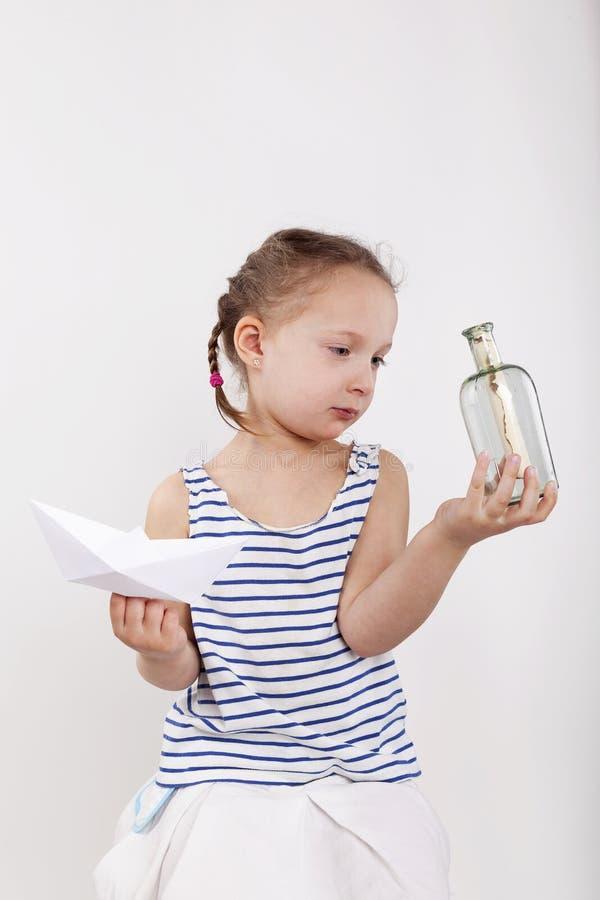 Mensaje secreto del hallazgo lindo de la niña en la botella de cristal imagenes de archivo