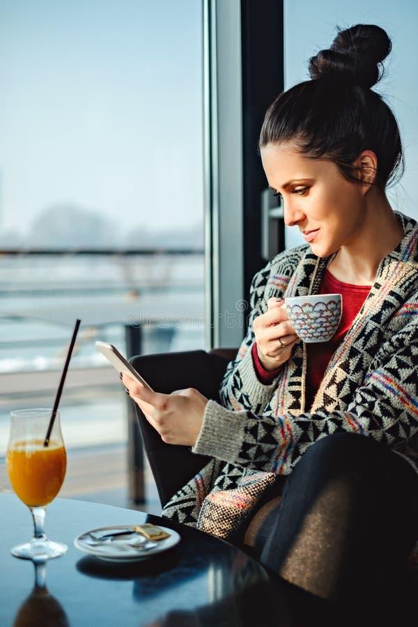 Mensaje sonriente de la lectura de la muchacha en el teléfono foto de archivo libre de regalías