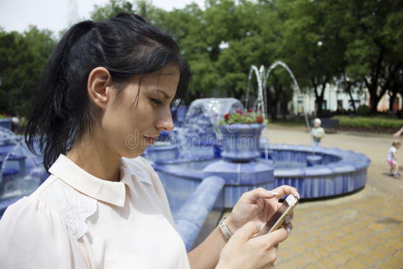 Mensaje texting de la muchacha en el teléfono fotos de archivo