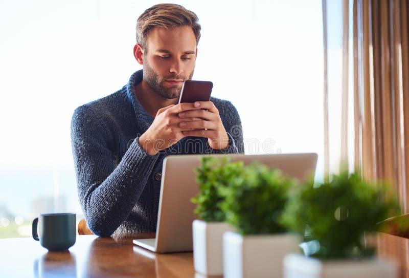 Mensajería adulta caucásica joven del hombre en su teléfono en casa imágenes de archivo libres de regalías