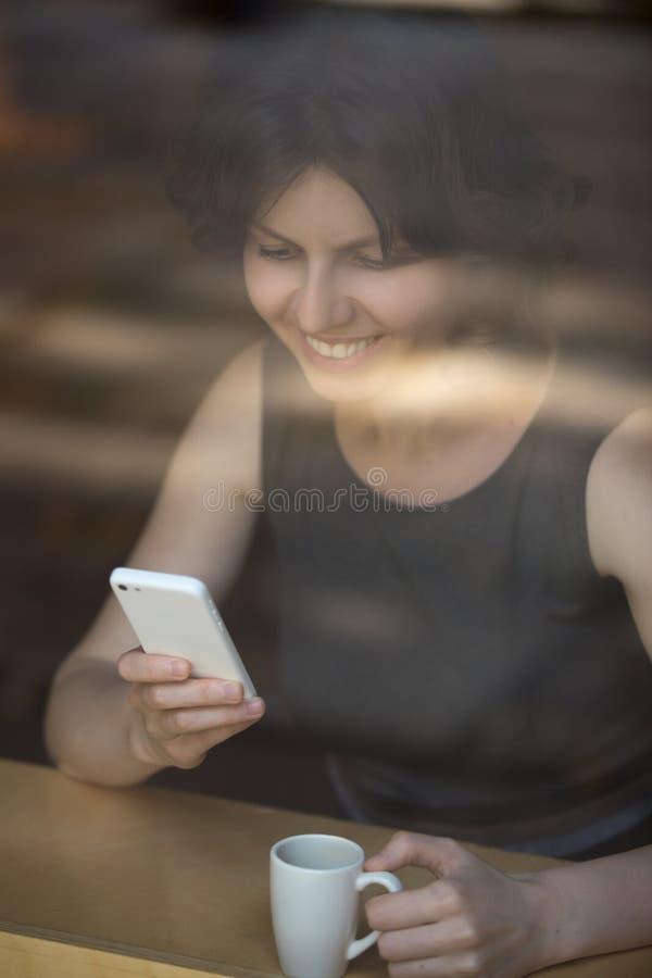 Mensajería de la mujer joven en café fotos de archivo