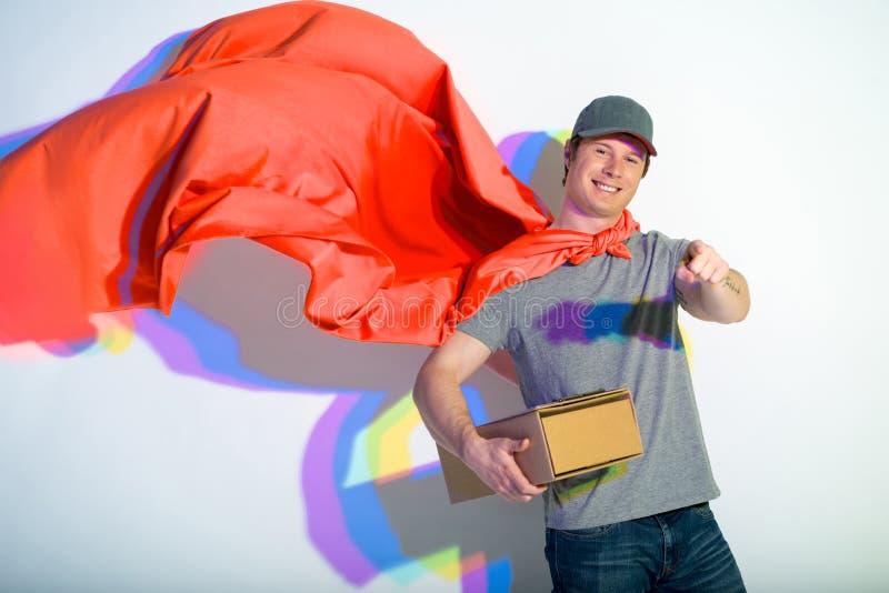 Mensajero alegre en el cabo rojo que guarda el paquete imagen de archivo libre de regalías