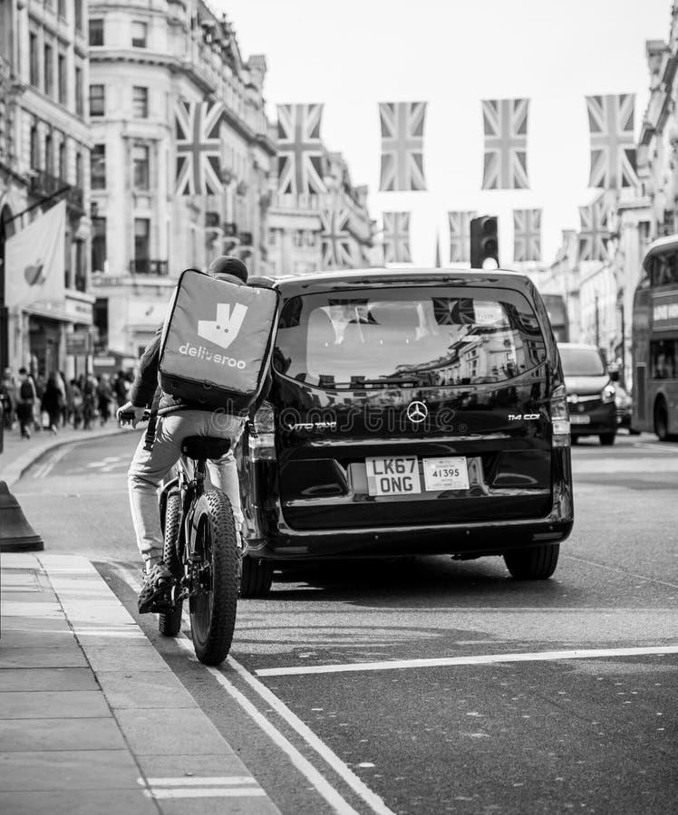 Mensajero de Deliveroo en la bici en la luz roja Regent Street fotografía de archivo