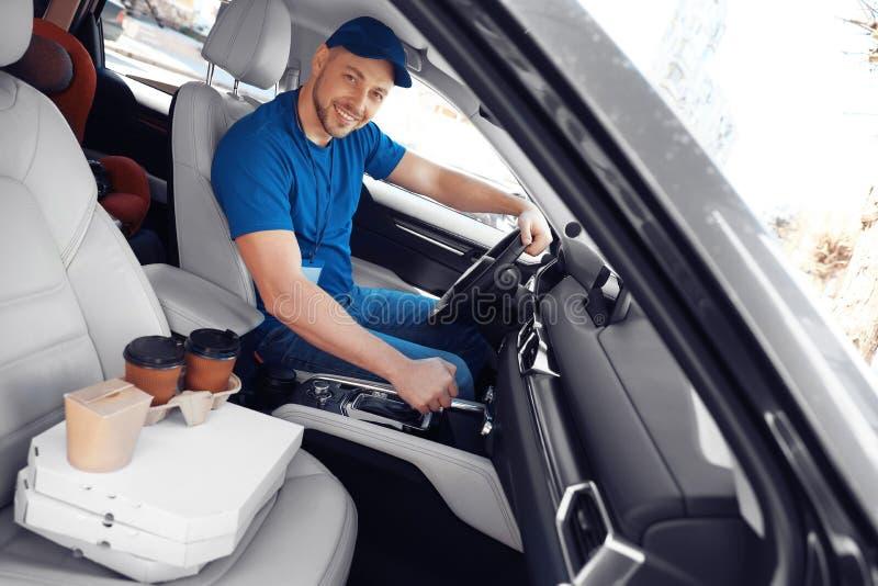 Mensajero de sexo masculino con órdenes en coche Entrega de la comida imagen de archivo