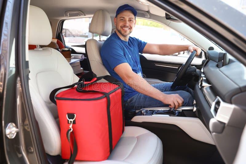 Mensajero de sexo masculino con el bolso termo en coche Entrega de la comida foto de archivo libre de regalías