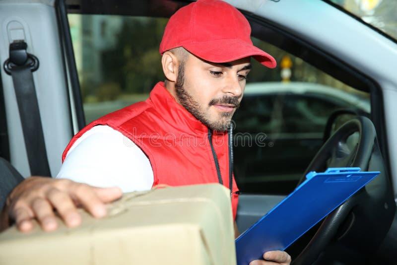 Mensajero joven que comprueba la cantidad de paquetes fotografía de archivo libre de regalías