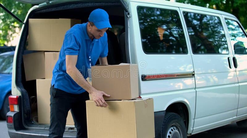 Mensajero que toma las cajas hacia fuera de la furgoneta de entrega, compañía móvil, envío de las mercancías fotografía de archivo libre de regalías