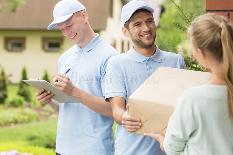 Mensajeros en uniformes azules y casquillos que dan el paquete a un cliente imagenes de archivo