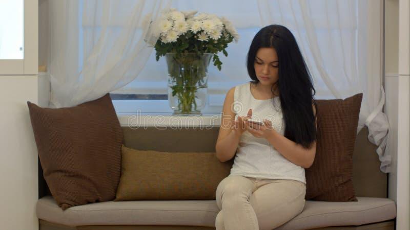 Mensajes de charla y que mandan un SMS de la empresaria joven en el teléfono móvil que se sienta en el sofá en casa imagen de archivo