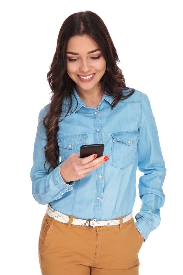 Mensajes felices de la lectura de la mujer joven en el teléfono móvil foto de archivo