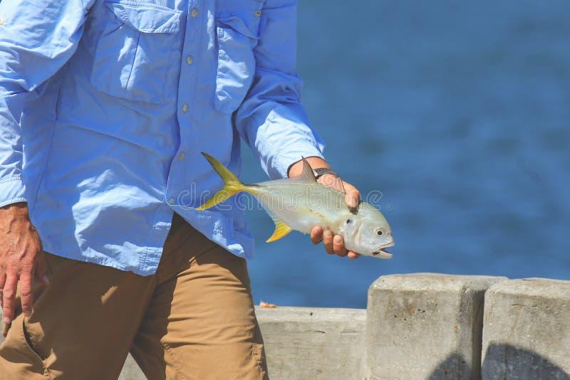 Mensch, der einen Fisch hält lizenzfreies stockbild