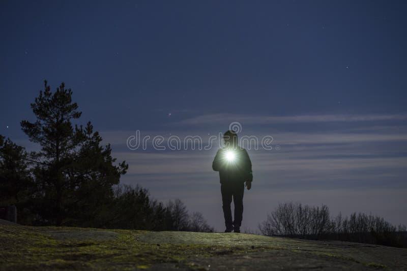 Mensch, der nachts mit Taschenlampe und Hoodie auf Kopf im Freien steht stockfotos