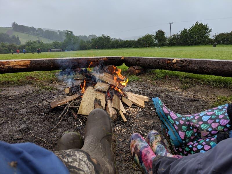 3 Menschen in den Paaren Gummistiefeln, die um ein Lagerfeuer sitzen stockbild