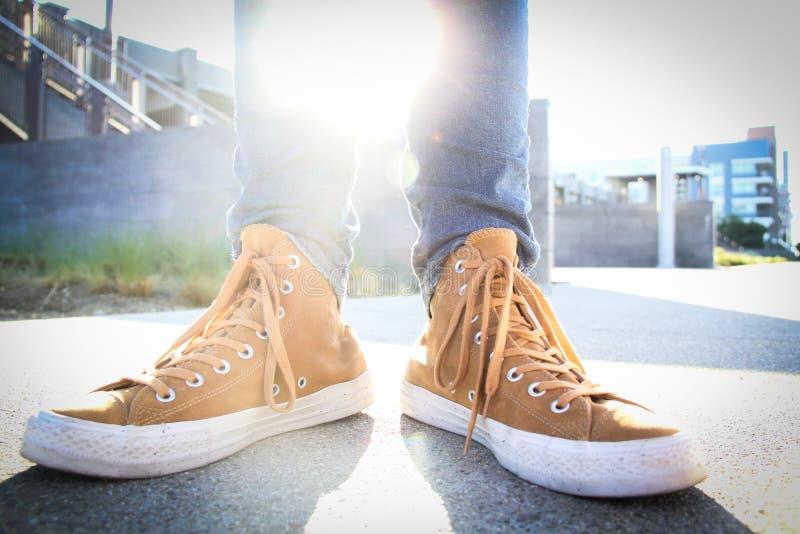 Menschen, die braune und weiße Sneakers der Spitzenklasse tragen stockbilder