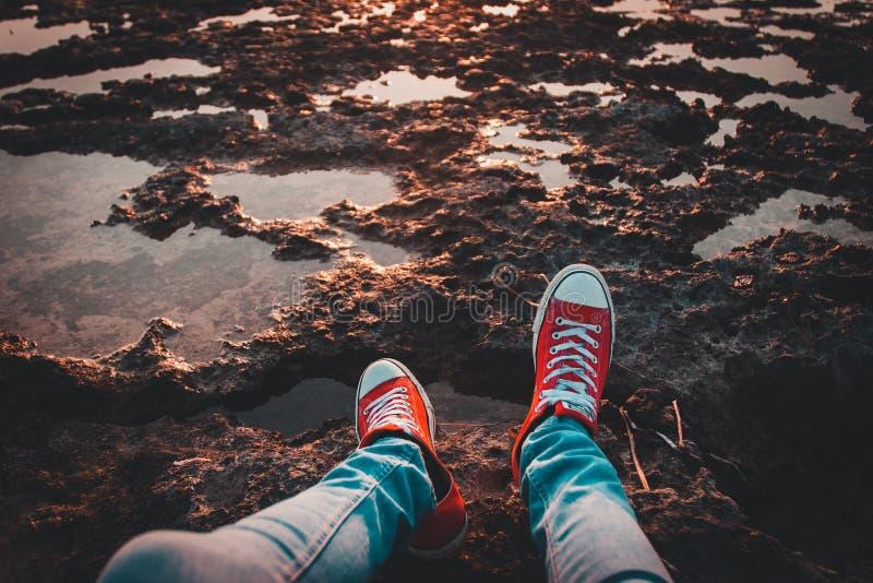 Menschen, die Rote Nieder-Top-Sneakers und Jeans tragen lizenzfreie stockbilder