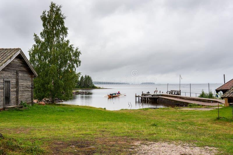 Menschen in einem traditionellen schwedischen Langboot, das an der Küste eines kleinen Fischerdorfes am See Siljan Schweden lizenzfreies stockbild