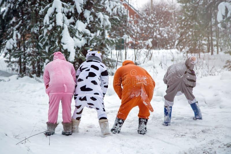 4 Menschen, 2 Mädchen und 2 Männer im kigurumi im Schneewinterwaldpyjamakostümschweinkuhkänguruh und -katze Spaß mit den Freunden stockfoto