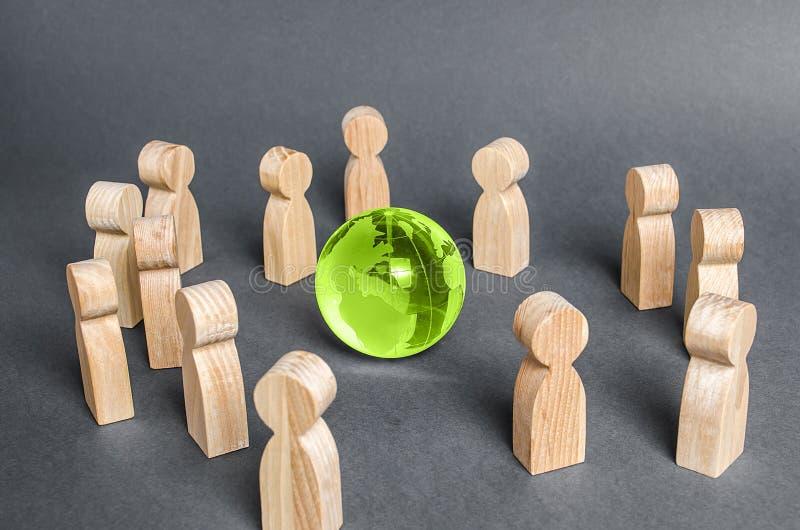 Menschen umgaben eine Glaskugel. Zusammenarbeit und Zusammenarbeit der Menschen in der ganzen Welt. Outsourcing und gemeinsame Pro stockfotos