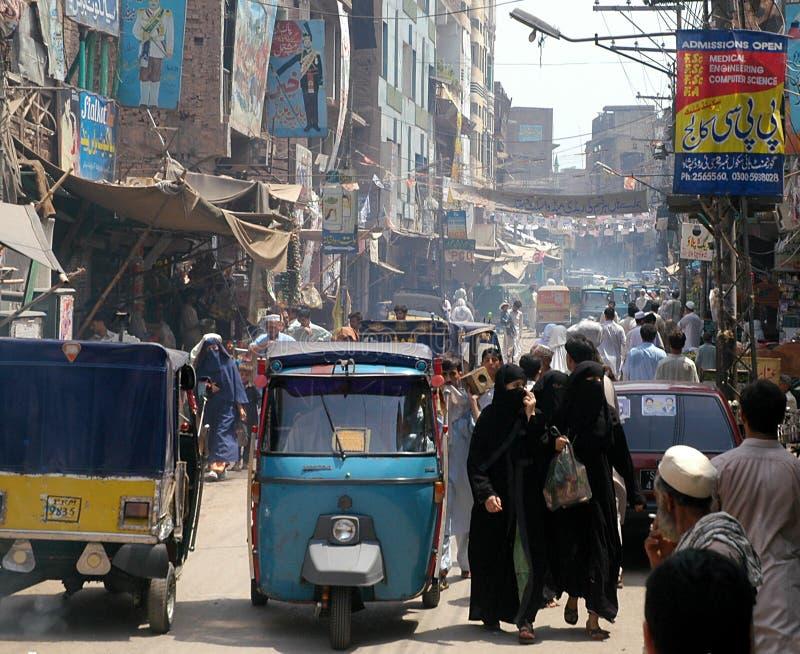 Menschen und Rikschas in einer belebten Straße in Peshawar, Pakistan lizenzfreie stockbilder