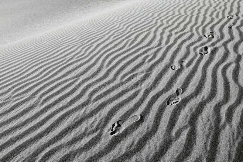 Menschenfußdrucke im Sand lizenzfreie stockbilder