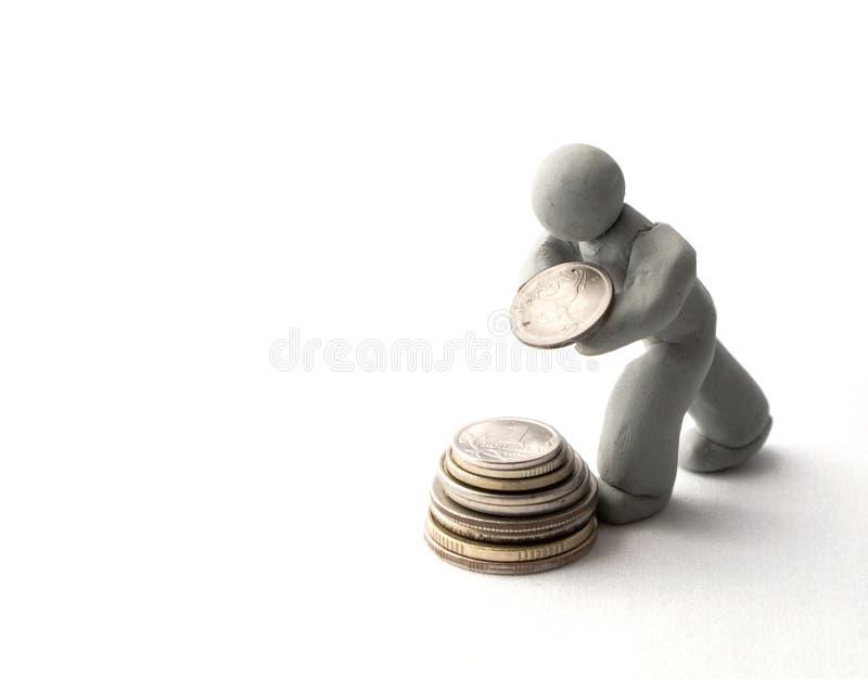Menschliche Abbildung des Plasticine baut eine Spalte der Münzen auf stockfotografie